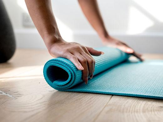 person rolling up yoga mat