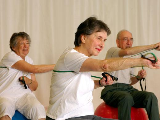 3 elderly people pushing arms forward while holding elastic straps