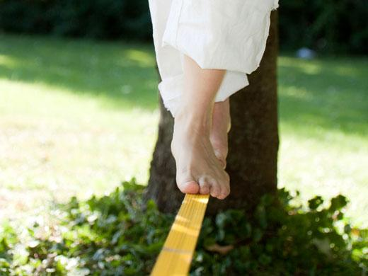 person walking barefoot on stretched strap