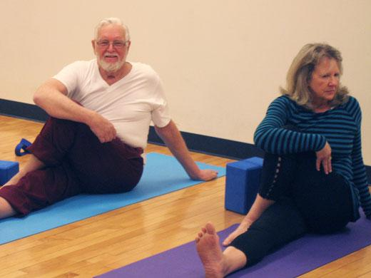 man and woman sitting, twisting their upper bodies