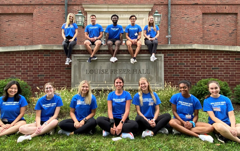 12 undergraduates in matching blue t-shirts sitting in front of Freer Hall